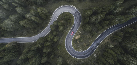 Birds eye view of a red car on a windy road